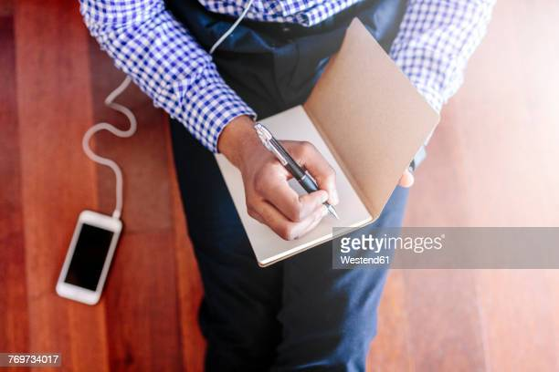 Man sitting on the wooden floor writing a note
