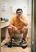 Man Sitting on Toilet
