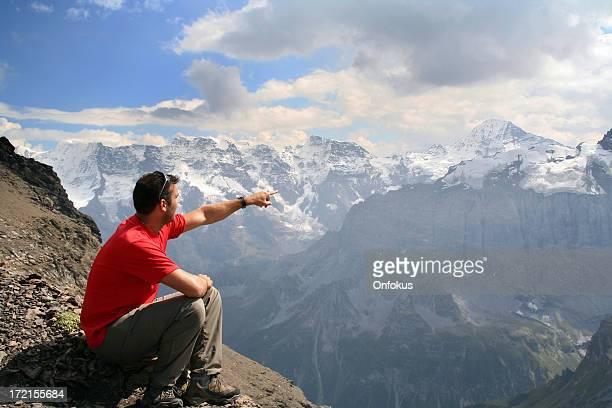 Mann sitzt auf der Spitze des Berges und zeigt eine Richtung
