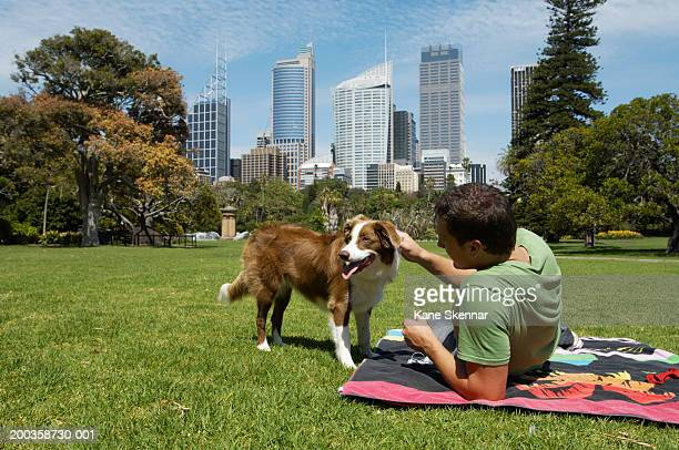 Man sitting on towel in park with border collie
