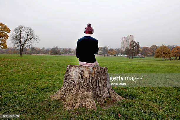Man sitting on tree stump listening to music