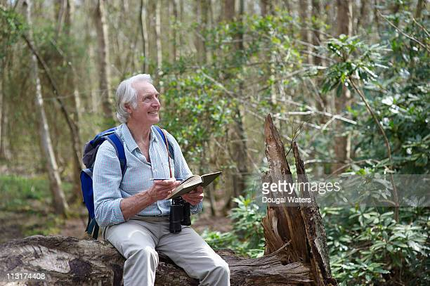 Man sitting on tree trunk and writing in book.