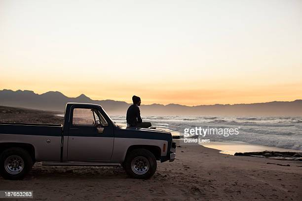 Man sitting on truck looking at ocean view
