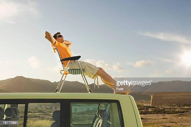 Man Sitting on Van Roof