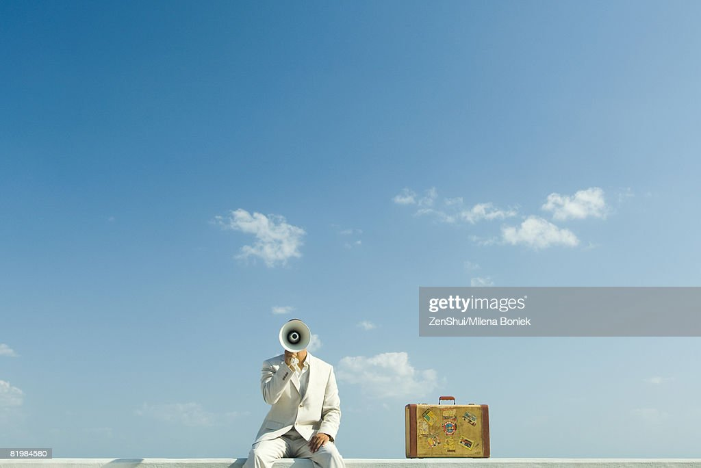 Man sitting on wall beside suitcase, holding megaphone in front of face