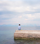 Man sitting on wall looking out to sea, rear view