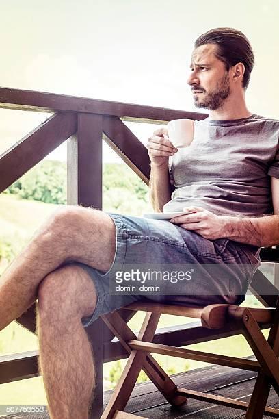 Mann sitzt auf hölzernen Stuhl, denken, wegsehen, trinken Kaffee