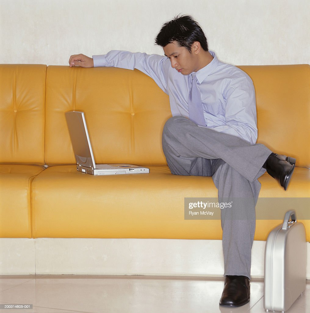 Man Sitting On Yellow Leather Couch Looking At Laptop Indoors : Stock Photo