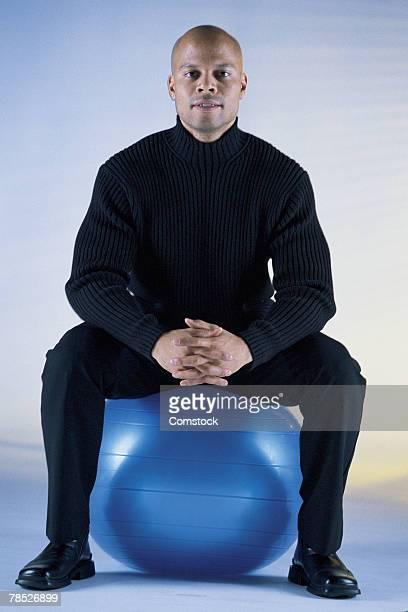 Man sitting on yoga ball