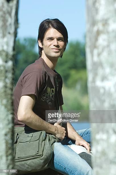 Man sitting outdoors wearing messenger bag