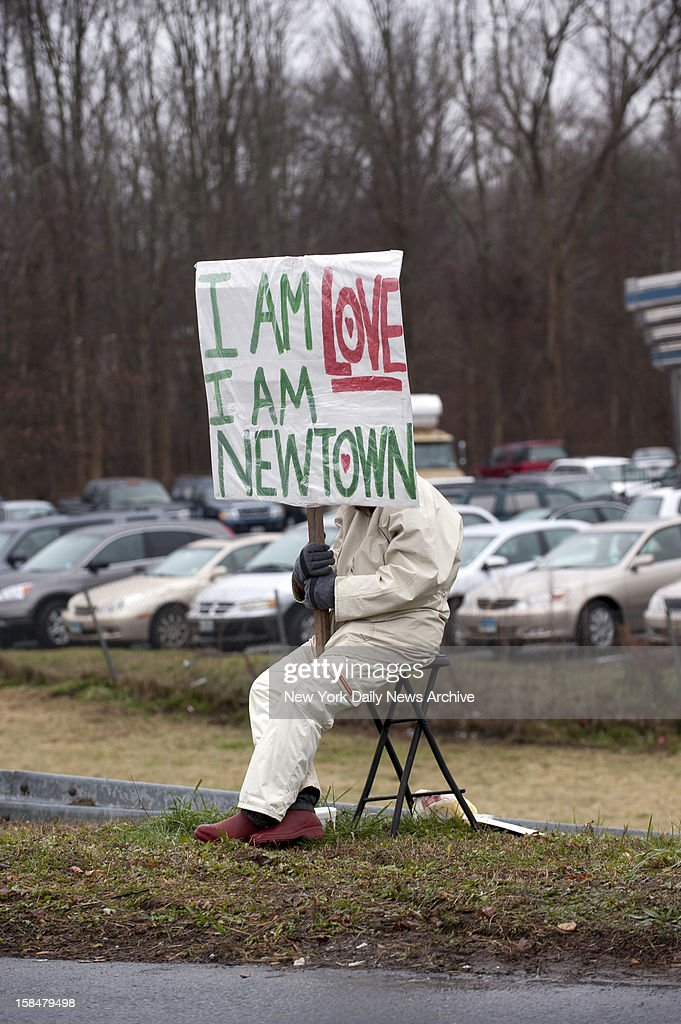 Man sitting outside Blue Colony Diner at Interstate 84 Exit 10 holds 'I Am Love I Am Newtown' sign.