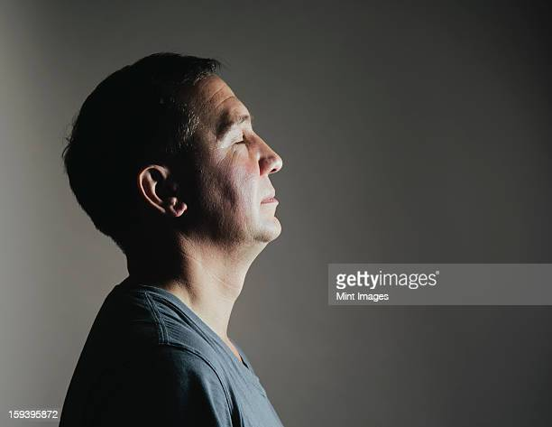 A man sitting still in repose with his eyes closed, viewed in profile.  A light source shining on his face.