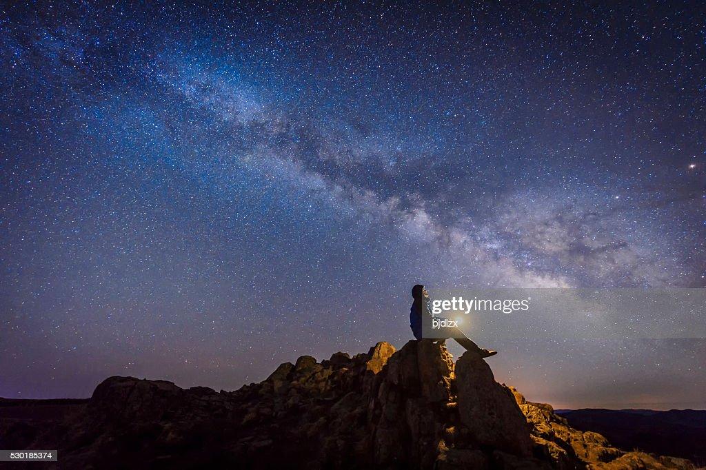 Man sitting under The Milky Way Galaxy : Stock Photo