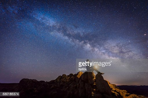 Man sitting under The Milky Way Galaxy