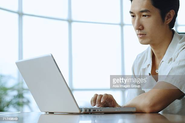 Man sitting, using laptop