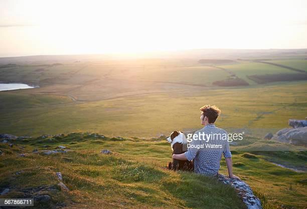 Man sitting with dog at sunset.