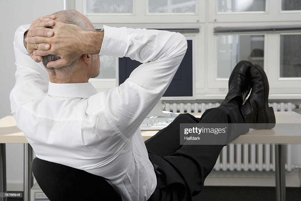 A man sitting with his feet up on a desk : Stock Photo