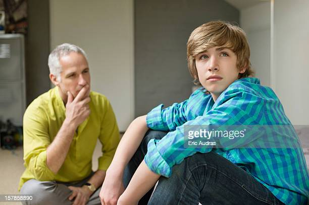 Man sitting with his son looking upset