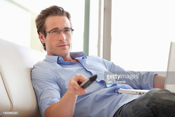 Man sitting with laptop changing channels with remote control