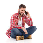 Handsome young man in jeans and lumberjack shirt sitting on floor with legs crossed and using a smart phone. Full length studio shot isolated on white.