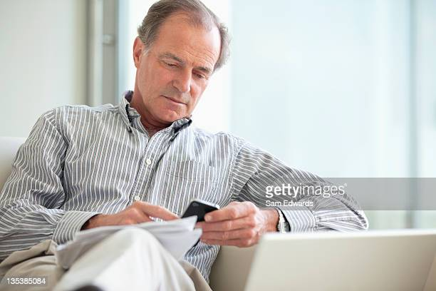 Man sitting with paperwork using cell phone