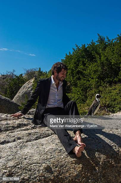 Man Sitting With Penguin On Rock Against Sky