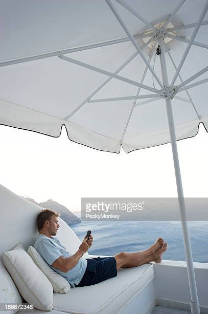 Man Sitting with Smartphone Texting Outdoors on Bright Seaside Balcony
