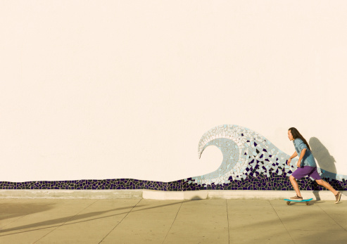 man skateboarding in front of a mosaic wave