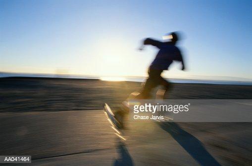 Man skating on  beach, at sunset