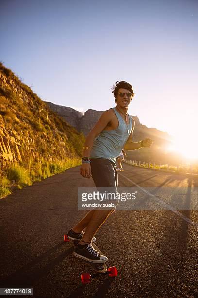 Homem longboard Skate Estrada ao pôr do sol