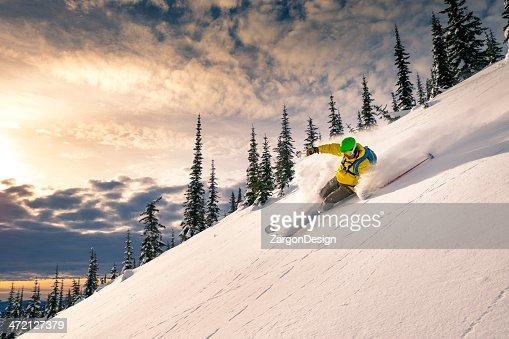 A man skiing down a powdery snow mountain