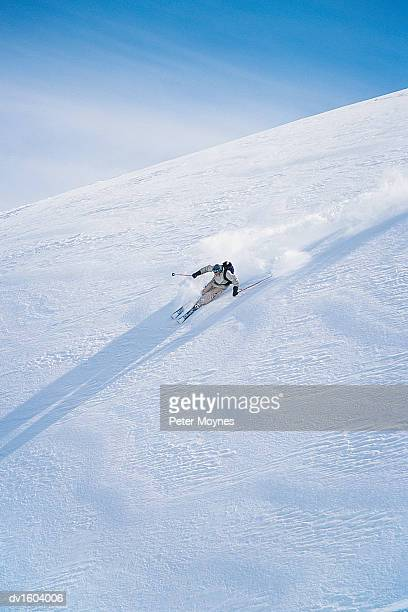 Man Skiing Down a Snow Covered Mountain
