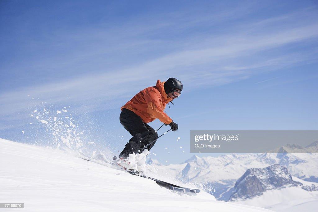 Man skiing downhill on mountain : Stock Photo