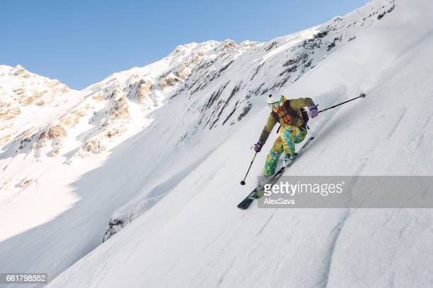 Man skiing downhill steep slope