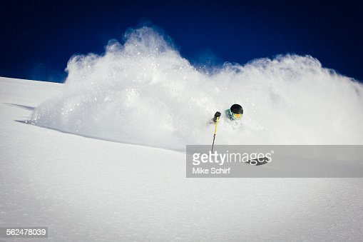 A man skiing powder on a beautiful sunny day in Utah
