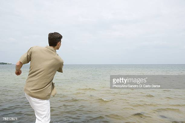 Man skimming stones at the beach, rear view