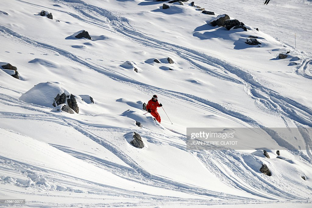 A man skis on December 31, 2013 in the French Alps ski resort of Meribel next to the rocky part between two slopes where German retired Formula One legend Michael Schumacher had an accident on December 29. Schumacher's condition has shown a slight improvement after a second operation following his weekend ski accident but he is not out of danger and being kept in a medically-induced coma, doctors said today. AFP PHOTO / Jean Pierre Clatot