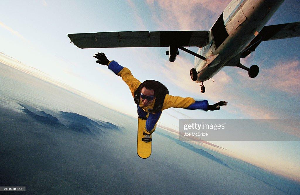 Man skyboarding over Lake Elsinore, plane overhead : Stock Photo