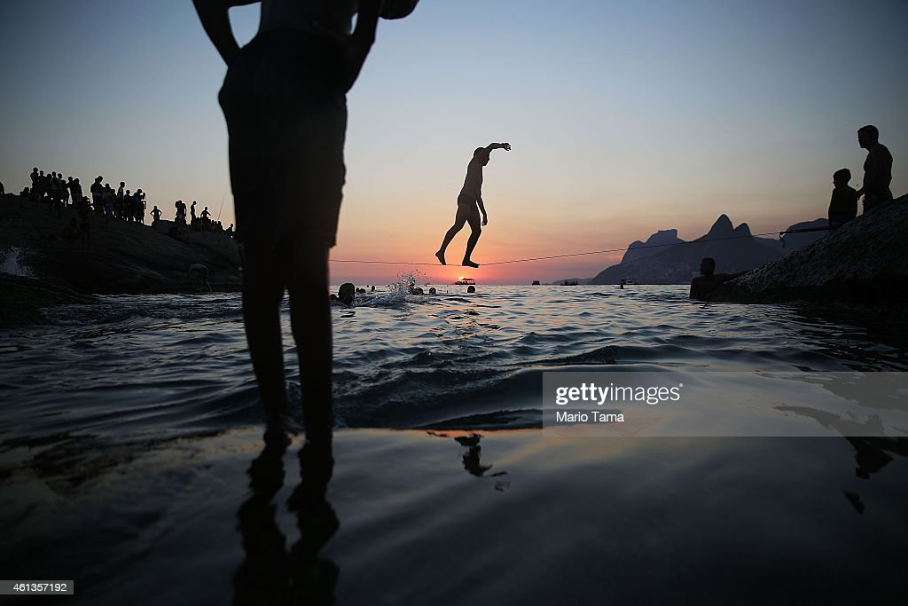 A man slacklines between the rocks at Arpoador on January 11, 2015 in Rio de Janeiro, Brazil. Rio residents flocked to the beach this weekend as summer temperatures soared.