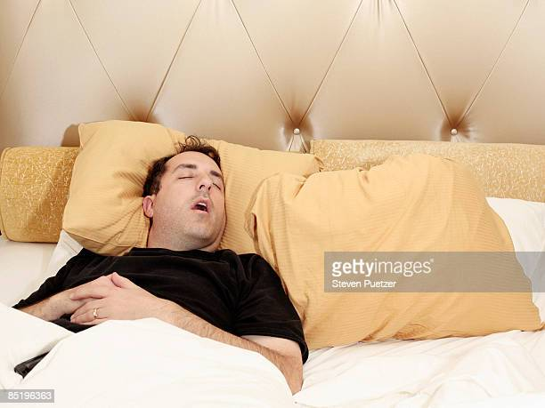 Man sleeping alone in bed