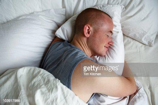 Man Sleeping And Hugging Pillow Smiling Stock Photo