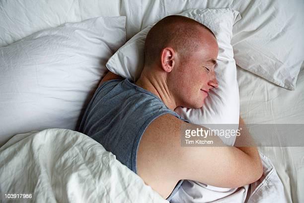 Man sleeping and hugging pillow, smiling