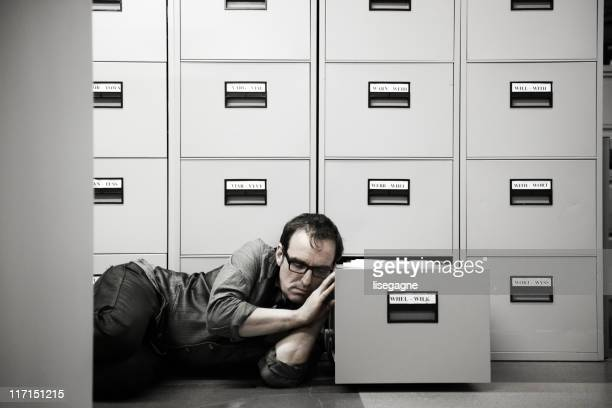 Man sleeping beside filing cabinet