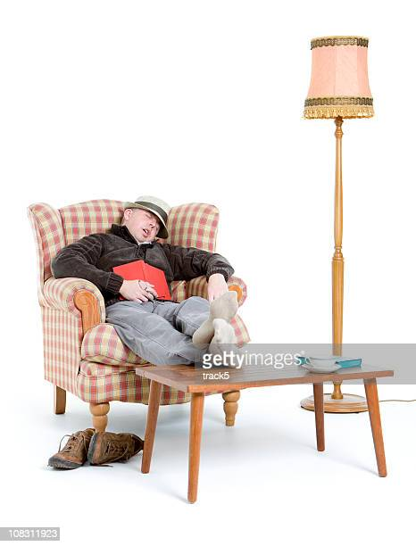 man sleeping in armchair while reading