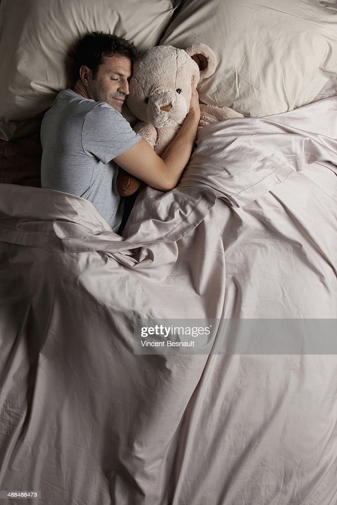 Man sleeping in bed with his teddy bear