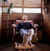 Man sleeping in cabin rocking chair, feet resting on stool