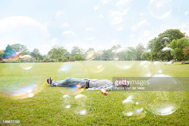 Man sleeping in grass, surrounded by bubbles..