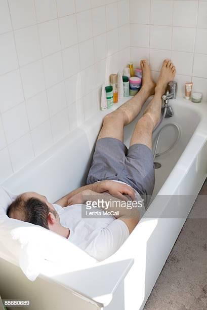 man sleeping in his bathtube