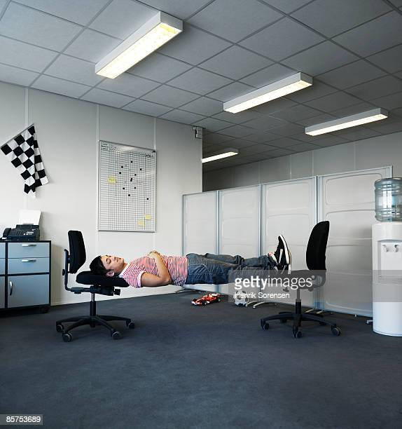 Man sleeping in his office on two chairs.