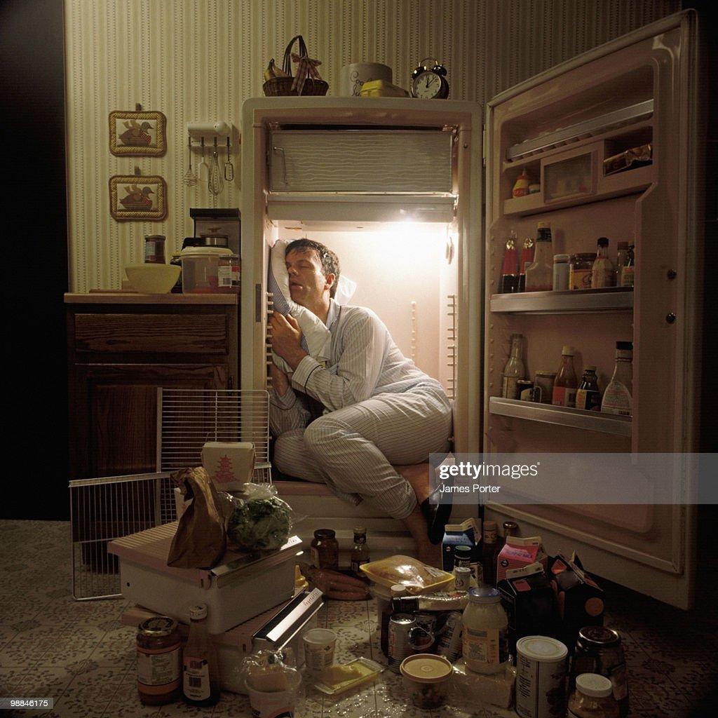 Man sleeping inside refrigerator
